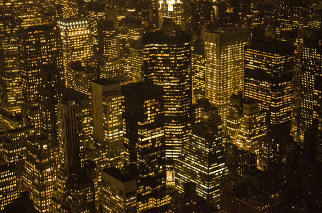 View of skyscrapers in Midtown Manhattan, New York with lights on at night